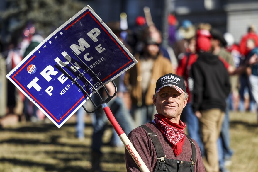 A Trump supporter holds a sign with a pitchfork as he protests the election outside the Colorado State Capitol on Jan. 6 in Denver.