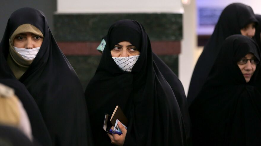 Iranian voters wear masks while waiting to cast their ballots in parliamentary elections Friday, on the outskirts of Tehran. Iranian health officials have reported at least five deaths linked with the novel coronavirus recently, adding jitters to a vote that suffered from relatively low turnout.
