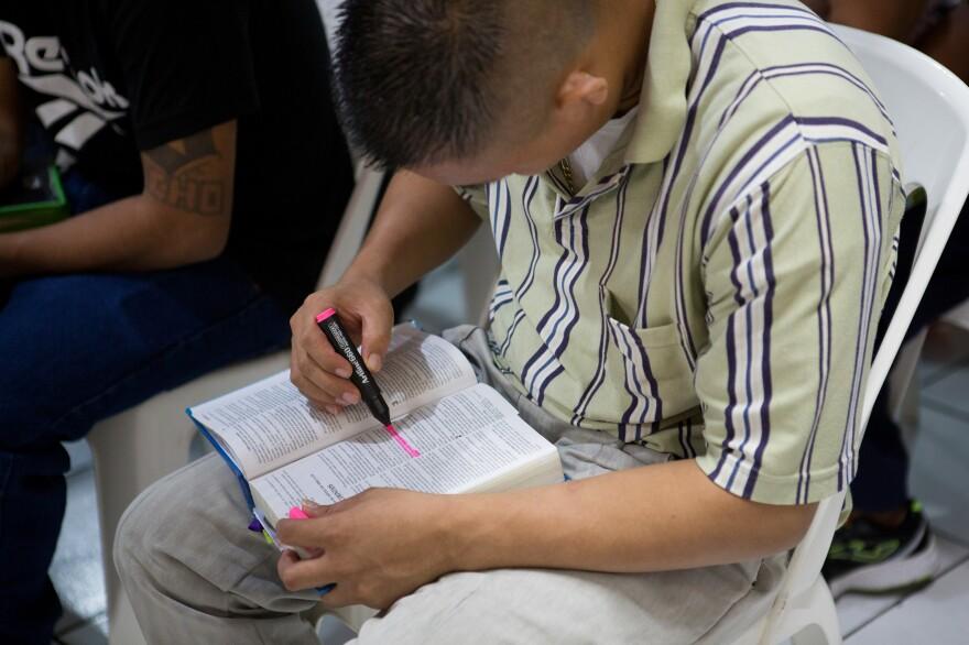 A former gang member highlights a Bible passage during a service at Eben-ezer.