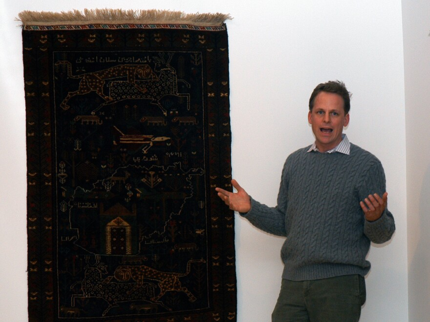"""Kevin Sudeith, shown at a 2005 exhibit in Davidson, N.C., collects, <a href=""""http://warrug.com"""">shows and sells Afghan war rugs.</a>"""