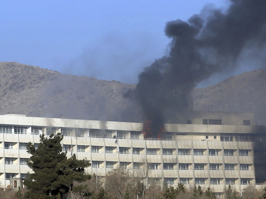 Men try to escape from a balcony of the Intercontinental Hotel after an attack in Kabul, Afghanistan, on Sunday.