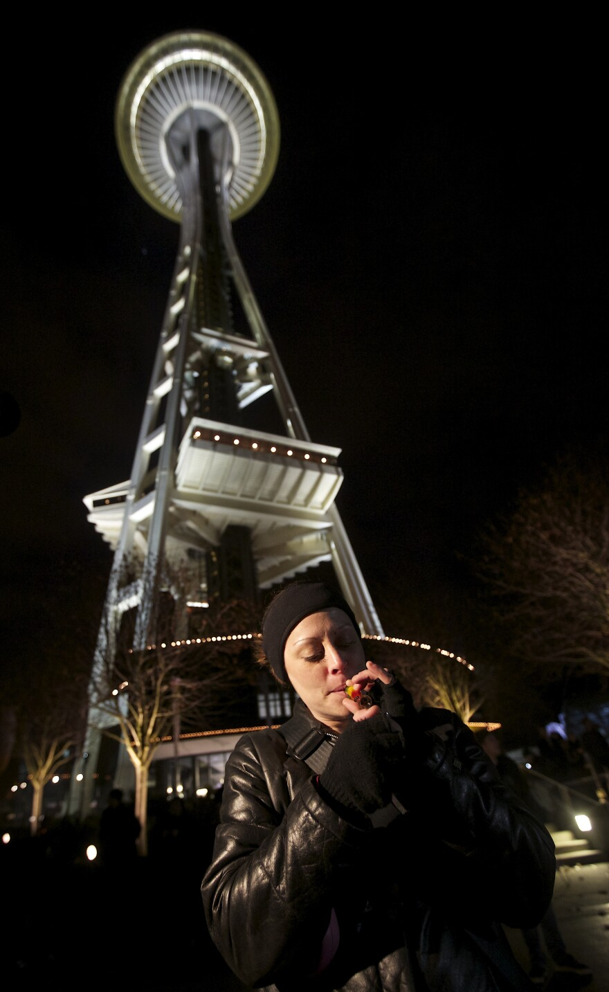 Robyn Bowen of Seattle Washington smokes marijuana underneath the Space Needle shortly after a law legalizing the recreational use of marijuana took effect on Thursday.