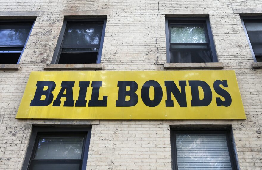A bail bonds sign hangs on the side of a bail bonds business. (Kathy Willens/AP)