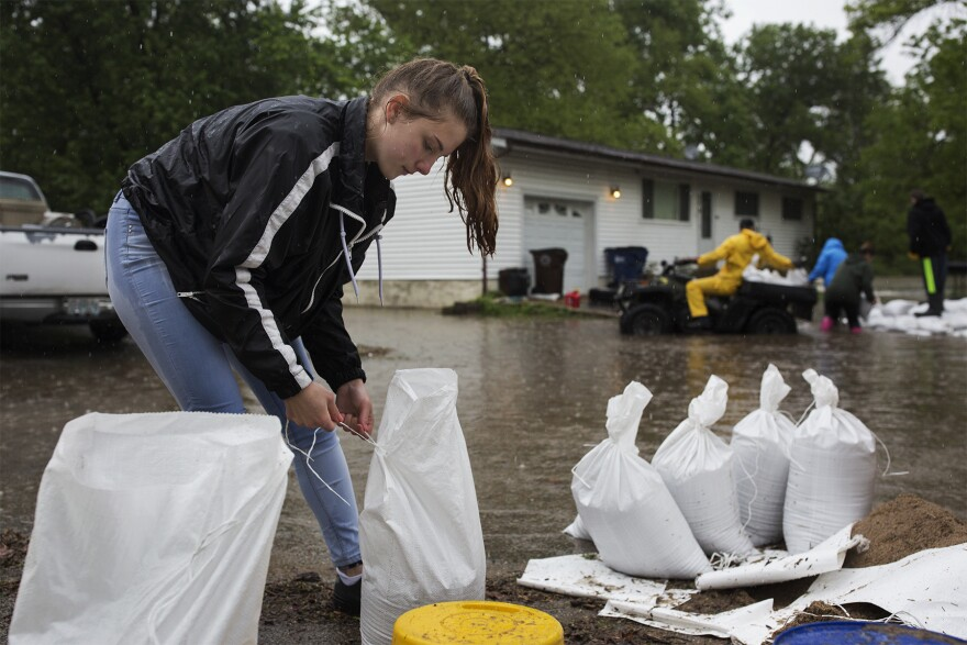 "Kaci Dalton, 16, helps residents fill sandbags on Starling Airport Road in Arnold. ""My other house used to flood so I know how it feels,"" she said. ""So I'm just trying to help out."""