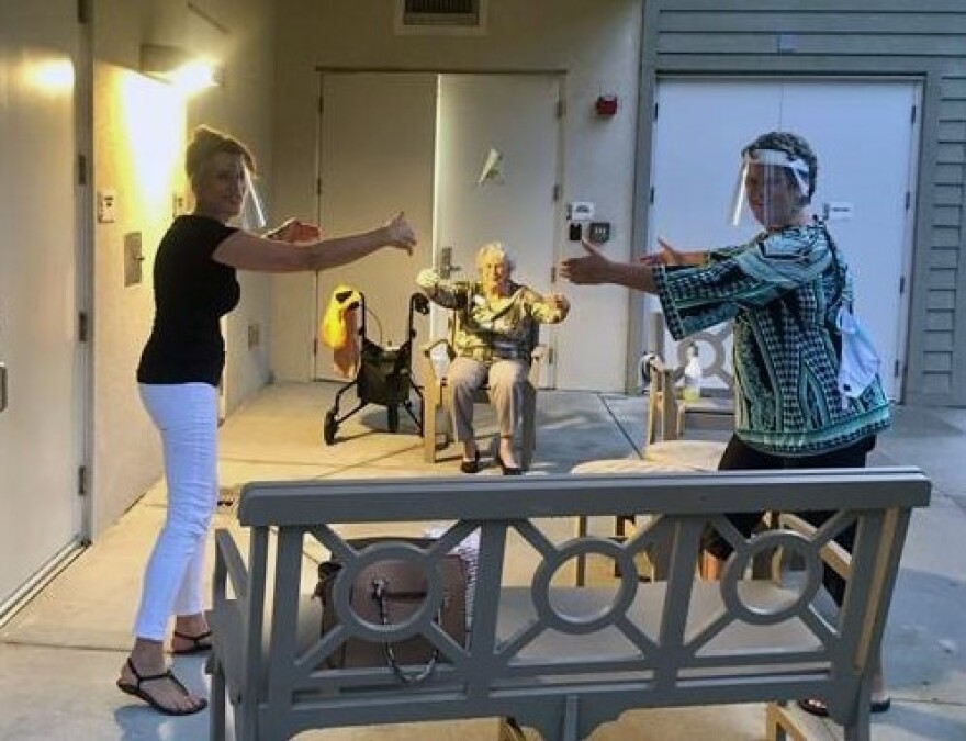 "Diane McMillen and her sister donned face shields and gave their mom an ""air hug"" from six feet away on the patio of a Tampa assisted living facility."