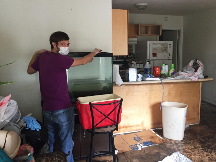 William Donelson transfers his fish from his aquarium after his apartment was flooded by Florence.