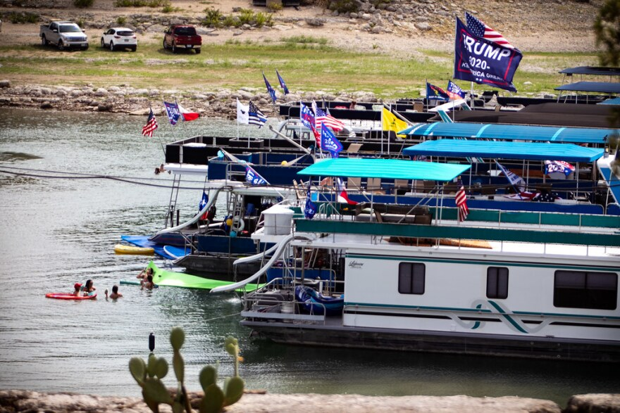 Boats with flags showing support for President Trump are docked in the marina at Emerald Point on Lake Travis on Saturday.