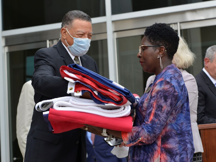 Reuben Anderson (left), former Mississippi Supreme Court justice, hands the Mississippi state flag to Pamela Junior, director of the Two Mississippi Museums, in Jackson, Miss., on July 1, after a bill was signed into law that would replace the state flag that includes a Confederate emblem.