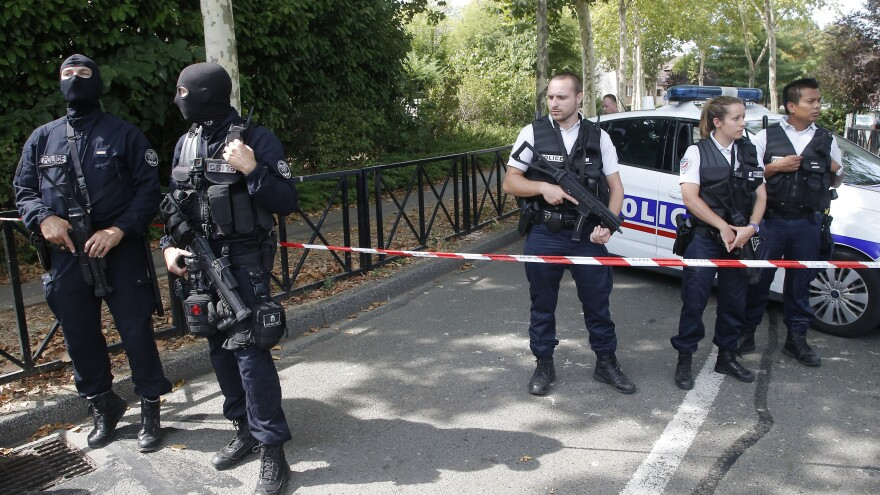 French hooded police officers guard the area with other police officers after a knife attack Thursday west of Paris.