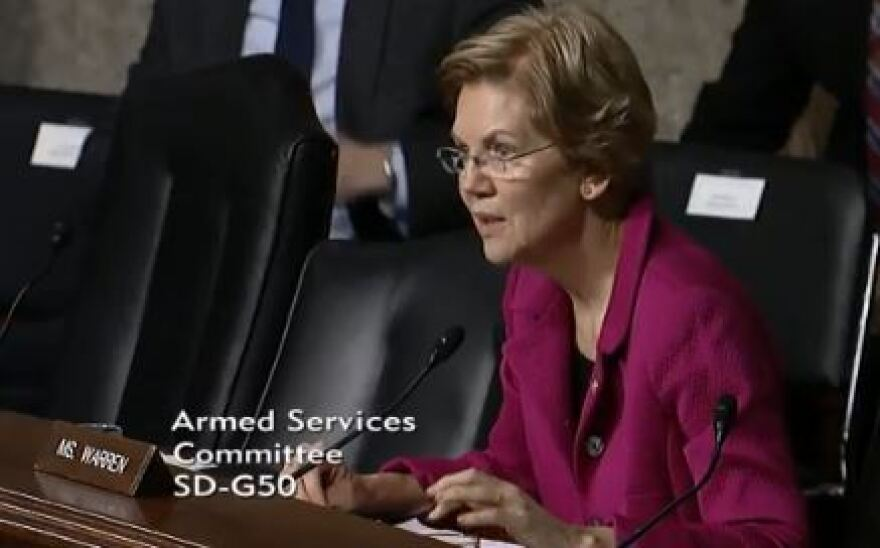 Senator Elizabeth Warren sits in her chair. Text laid over the image reads Armed Services Committee SD-G50
