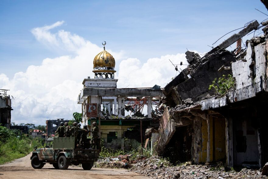Soldiers on a military truck drive past destroyed buildings in Marawi last year.