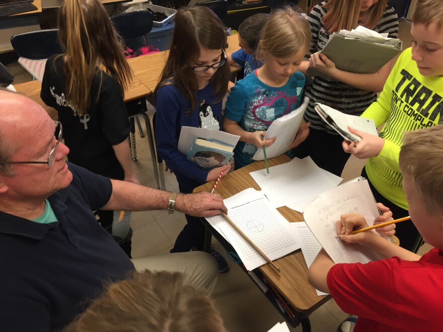 Students step back inside the classroom with their teacher Jim Jenkins to graph out the best locations in the soil to plant their seeds.