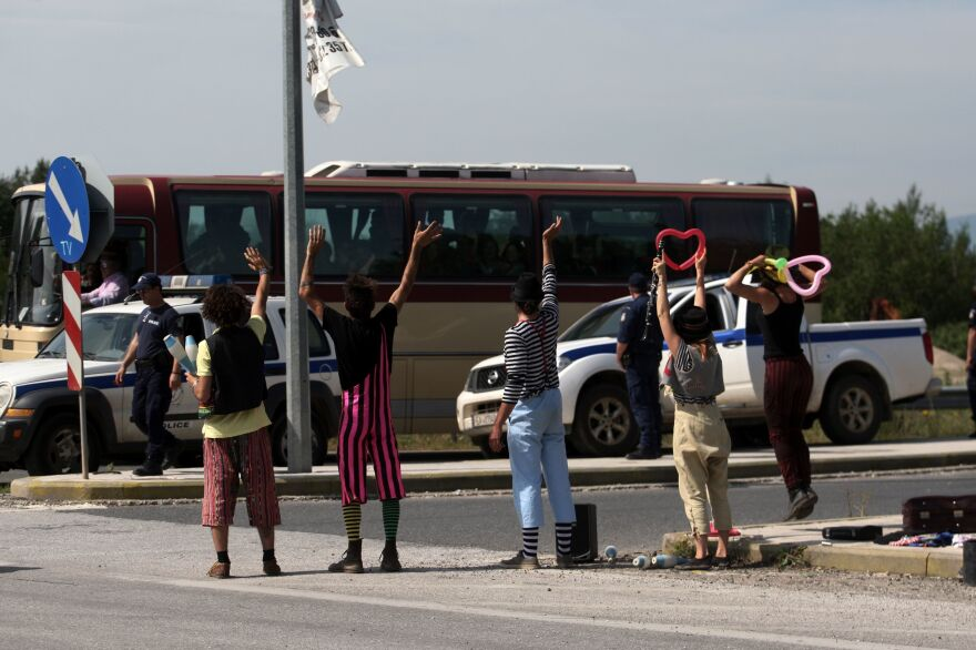 Clowns from a solidarity group wave to migrants on a bus during the evacuation of the Idomeni camp on Tuesday. Hundreds of people were put on buses heading to newly opened camps in the vicinity of Thessaloniki, Greece, about 50 miles to the south.