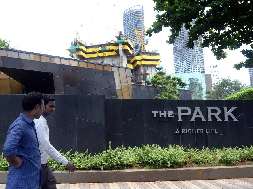 "Men walk past Mumbai's ""Trump Tower"" in July 2015. It is still under construction."