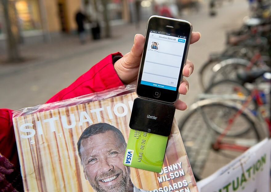 Nina Galata displays her smartphone equipped with a card reader to accept donations and payment for <em>Situation Stockholm,</em> a magazine sold by Stockholm's homeless.