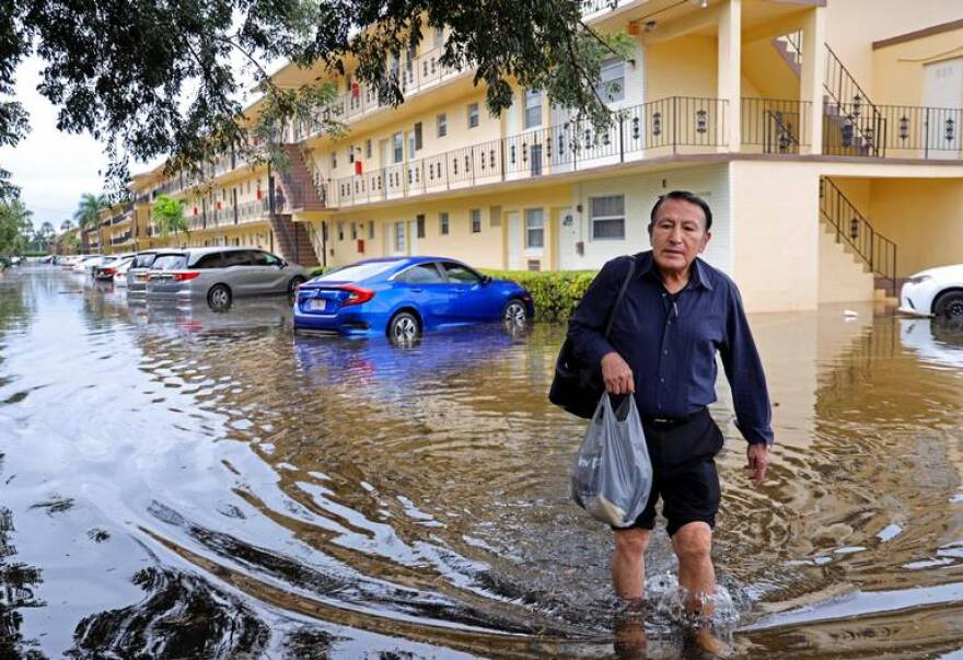 A man walks through a flooded area in front of an apartment complex. The water reaching just below his knees.