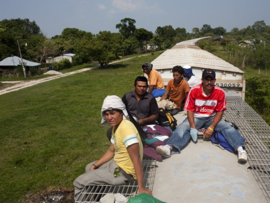 Migrants ride on top of a freight train that left from Tenosique, Tabasco.