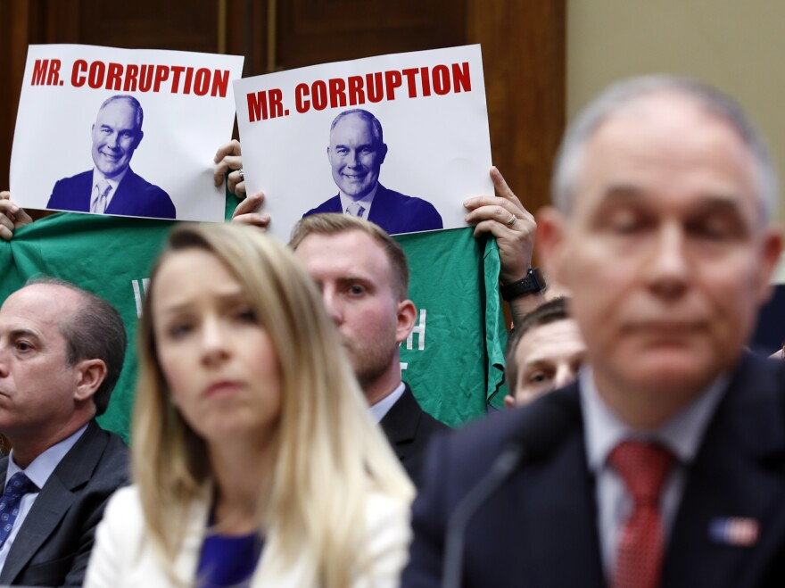 Protesters hold up signs and shirts behind then-Environmental Protection Agency Administrator Scott Pruitt while testifying on Capitol Hill in April. Pruitt was one of a handful of Trump administration officials forced to resign while facing ethics investigations this year.