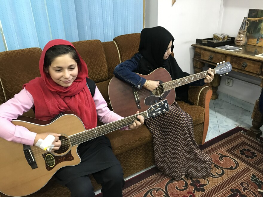 "Sixteen-year-old Madina Mohammadi (right), with Mursal, never attended school before teaming up with Cordola. The guitar lessons ""teach me a little bit too about life,"" she says."