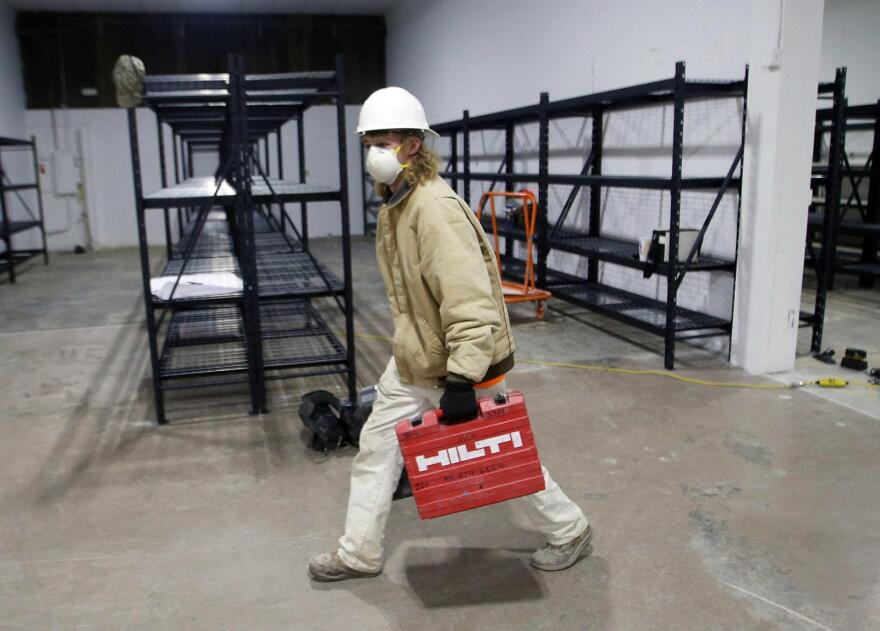 A construction worker carried tools past metal shelves built to hold bodies in an overflow morgue, the Dignified Transfer Center, in Earth City on April 17, 2020.