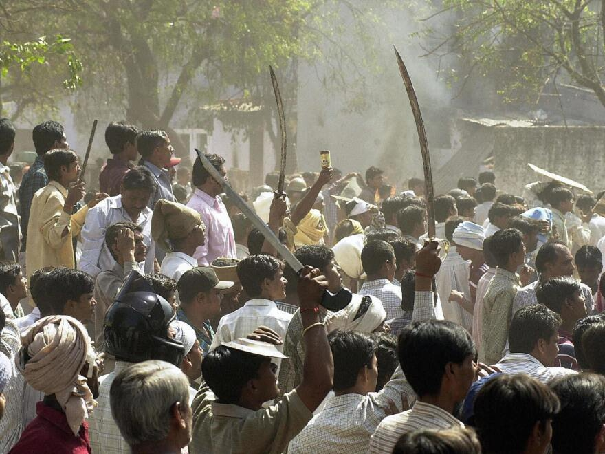 A Hindu mob waves swords at an opposing Muslim mob during communal riots in Ahmedabad in 2002.