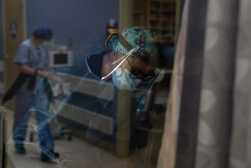 A photograph of a nurse in full protective equipment photographed through a window as she cares for a patient.