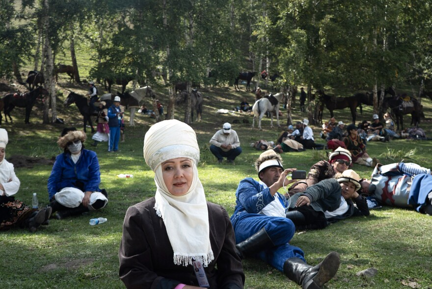 A Kyrgyz woman from the southern part of the country (center) and other onlookers watch the Nomad Game events.