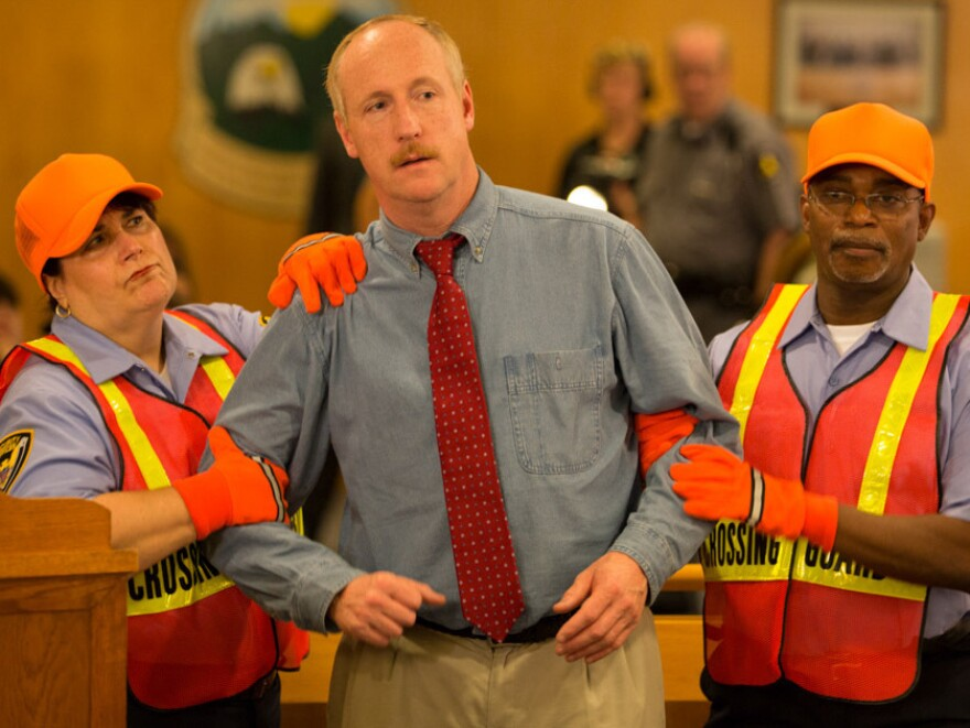 Dave (Matt Walsh, center) unwittingly enjoys a ride of fame after a dust-up at a town hall. This, of course, angers his fame-hungry daughter to no end.
