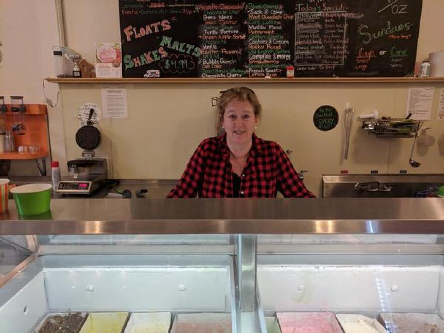 Karen Soeffker stands behind an ice cream freezer she says wouldn't exist without current green-energy city policies.