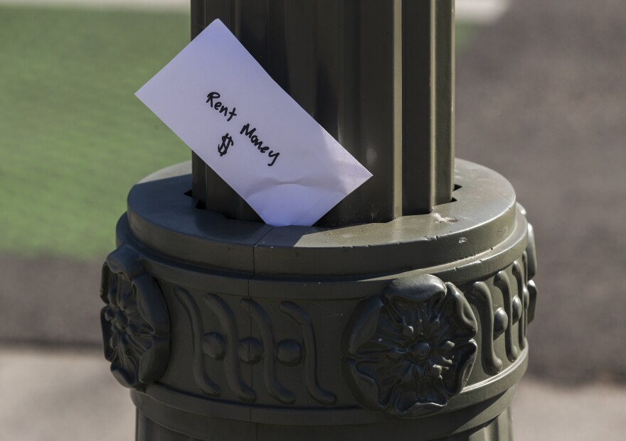 "A paper envelope written with the words ""Rent Money $"" is left tucked in a lighting pole in the Boyle Heights east district of the city of Los Angeles."