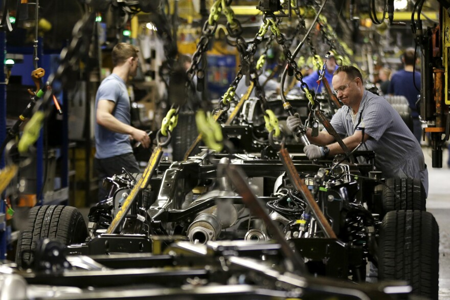 In this March 13, 2015, file photo, a worker prepares a chassis to receive an engine on a new aluminum-alloy body Ford F-150 truck at the company's Kansas City Assembly Plant in Claycomo, Mo. (Charlie Riedel/AP)