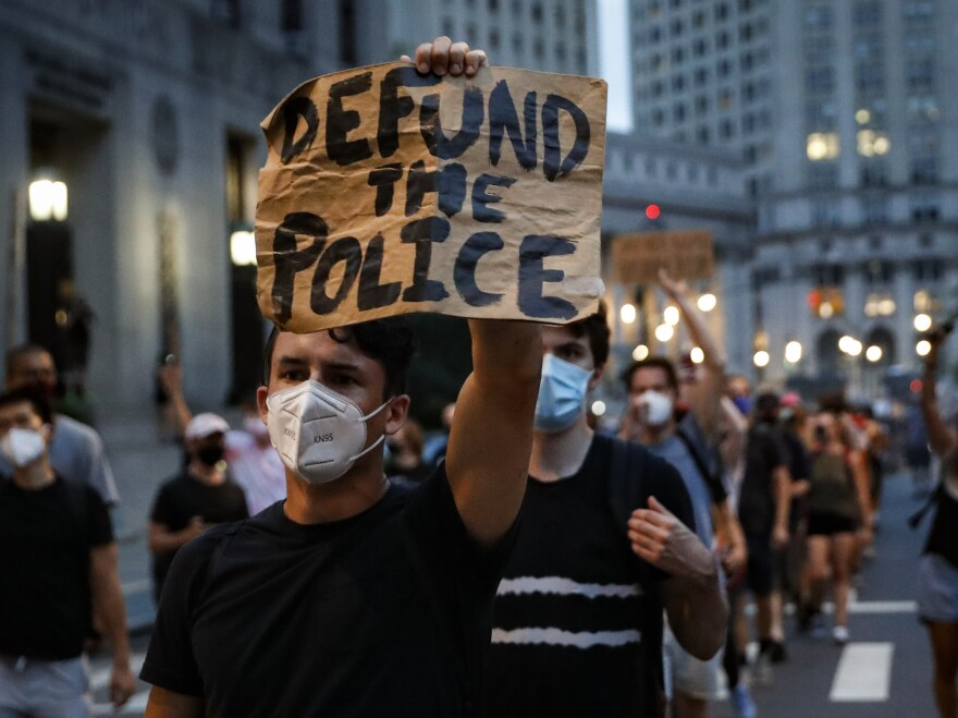 "This photo from Thursday July 30, 2020, shows a demonstrator holding a sign that reads ""Defund the police"" during a protest march in New York."
