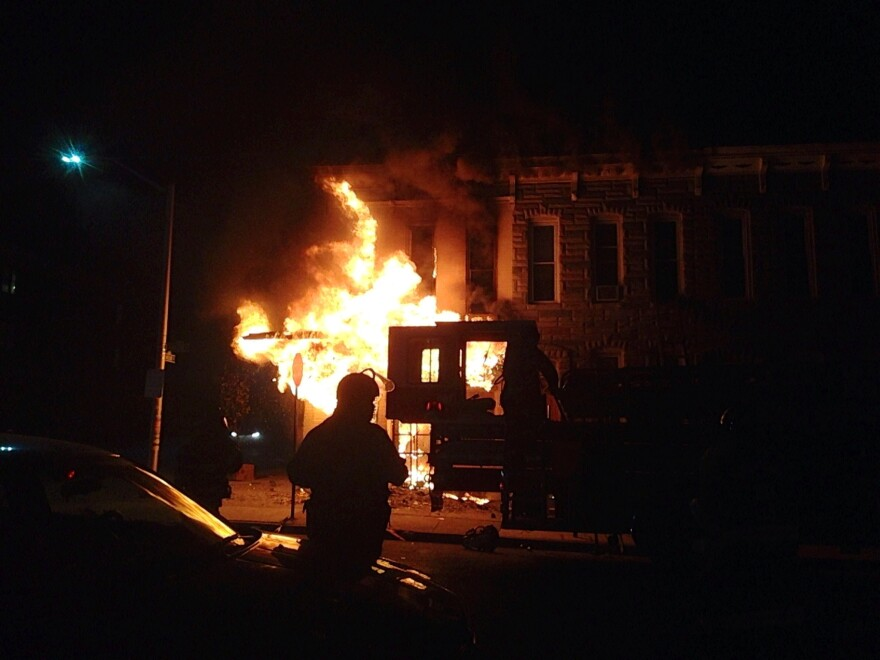 A police officer watches a corner market burn in the west side of Baltimore.
