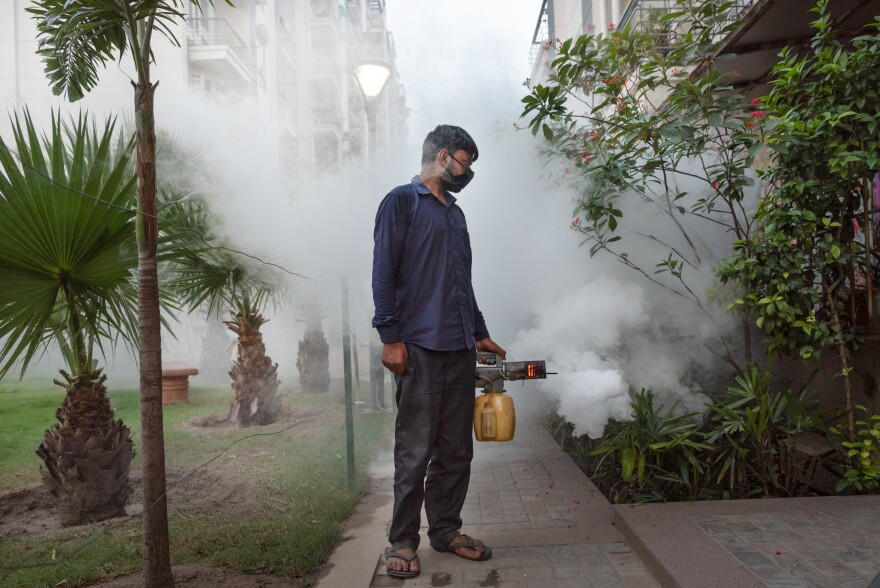 Maintenance and security staff, whose work is often unnoticed and unappreciated, are risking their lives to ensure a safe and healthy environment for all of us. I took this image as one of the workers fumigated the park, which is usually busy at this time of the evening with residents exercising and doing yoga. <em>April 24, 2020. Delhi, India.</em>