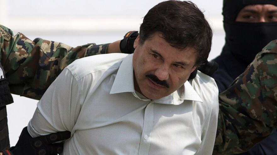 """Joaquin """"El Chapo"""" Guzman is escorted to a helicopter in handcuffs by Mexican navy marines at a navy hanger in Mexico City on Saturday. A senior U.S. law enforcement official said that Guzman, the head of Mexico's Sinaloa Cartel, was captured alive overnight in the beach resort town of Mazatlan."""