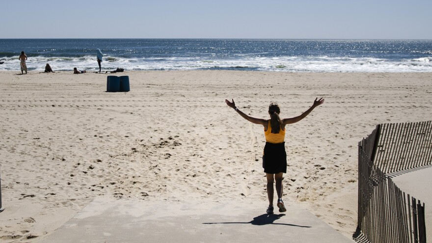The Jersey Shore is central to the state's identity, Gov. Phil Murphy said Thursday, announcing that all New Jersey beaches can reopen soon. Here, a woman walks on the beach this month in Belmar, N.J.