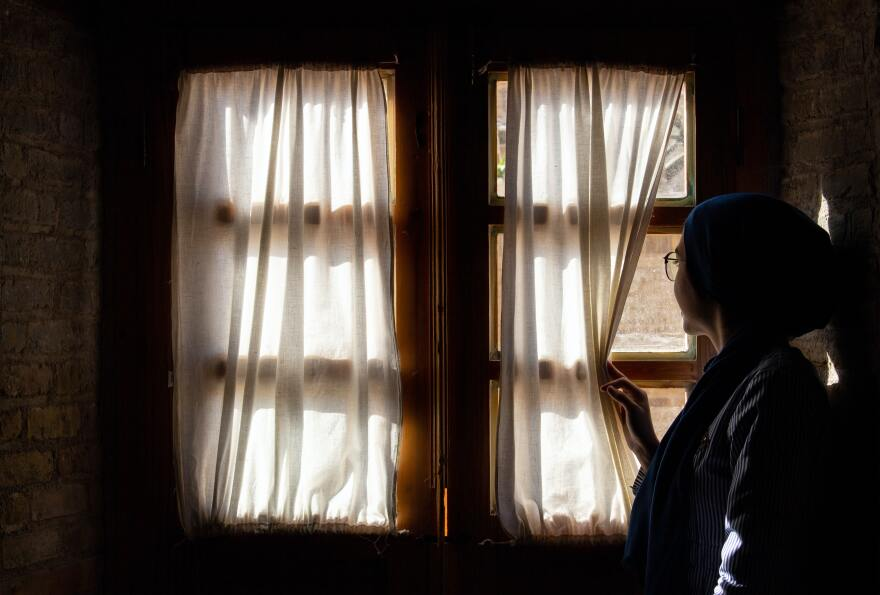A woman in a dark room pushes aside curtains to look out a window.