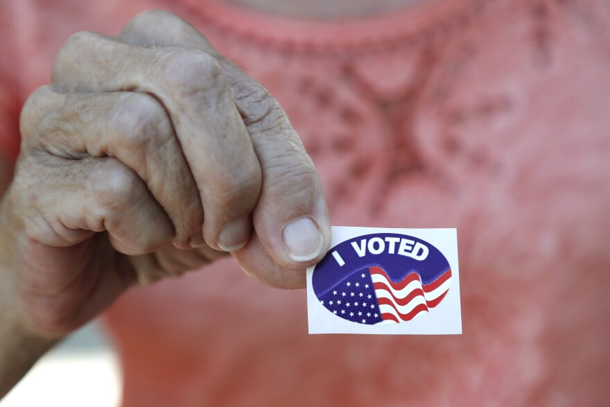"""Close up view of a sticker with the American flag on it. Above the flag are the words, """"I voted."""""""