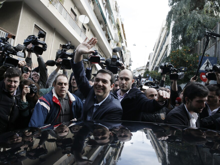 Alexis Tsipras, center, leader of Greece's Syriza left-wing main opposition waves to his supporters after voting at a polling station in Athens on Sunday.