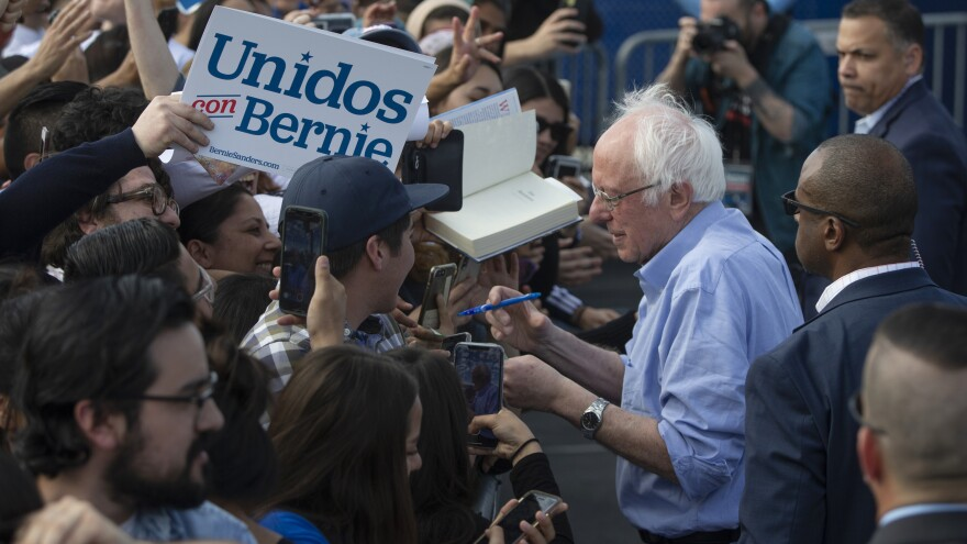 Sen. Bernie Sanders signs autographs at a February campaign event with Latino supporters in Santa Ana, Calif. Some Democrats say the Biden campaign can learn from Sanders' outreach.