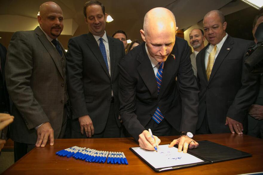 Gov. Rick Scott signs a bill in 2014. A conservative-advocacy group is telling Gov. Rick Scott it'll have his back if he vetoes projects crammed into the state budget just before the nearly $80 billion package was completed last week.