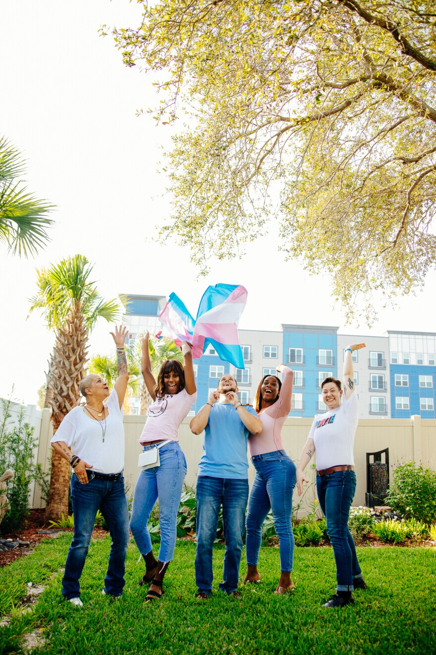 Five people stand in a garden holding up a trans pride flag in the colors of light blue,  pink and white.