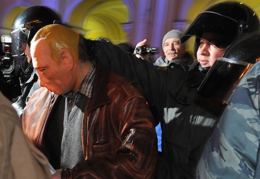 Riot police officers detain a man in a mask depicting Russia's Prime Minister Vladimir Putin during an opposition protest in St. Petersburg on Thursday.