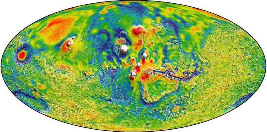 A Martian gravity map shows the Tharsis volcanoes and surrounding flexure. The white areas in the center are higher-gravity regions produced by the massive Tharsis volcanoes, and the surrounding blue areas are lower-gravity regions that may be cracks in the crust (lithosphere).