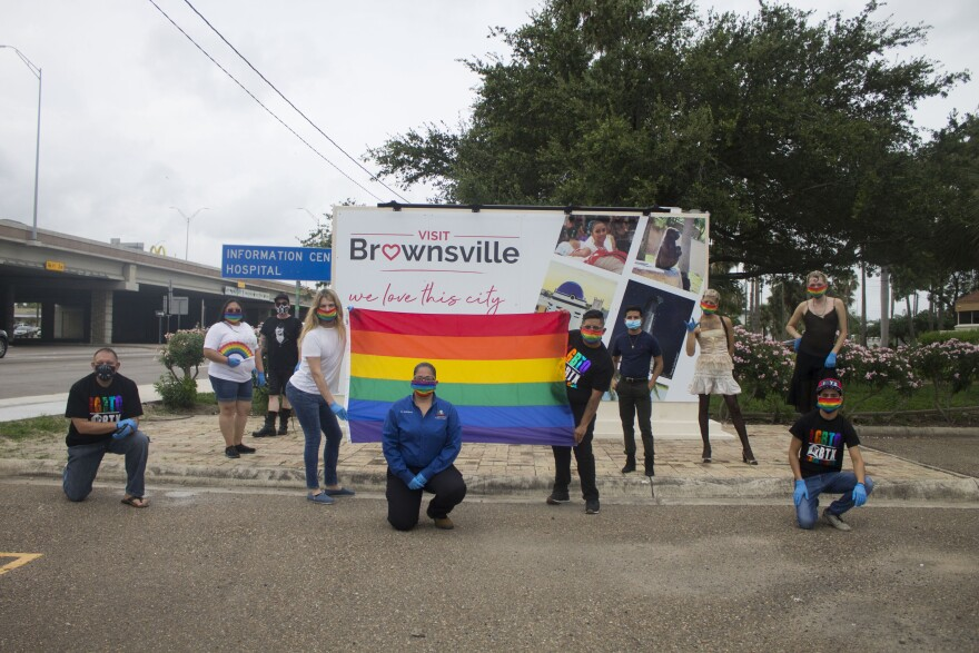 A group of Brownsville residents pose at a LGBTQ+ flag raising ceremony.