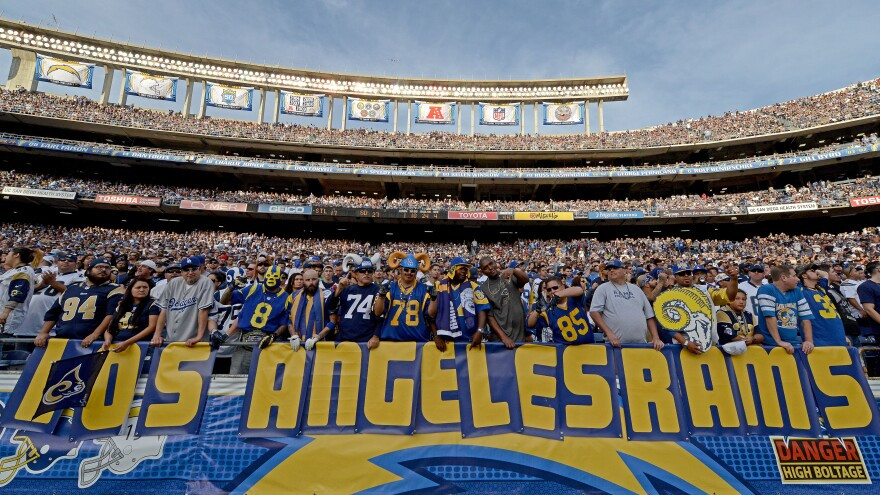 """Fans hold a """"Los Angeles Rams"""" sign during a San Diego Chargers game against the St. Louis Rams last year. Both teams are part of proposals to build new NFL stadiums in the LA area."""
