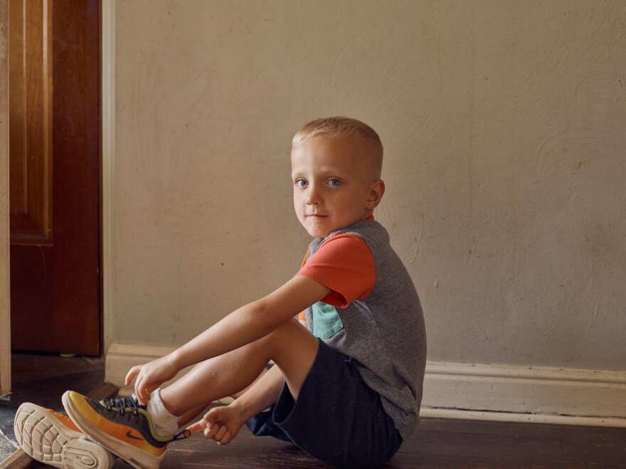 Liam Zuger puts on his shoes before going outside to play with his family. By age 4, Liam had developed all five proteins that indicate he's at high risk of developing Type 1 diabetes.