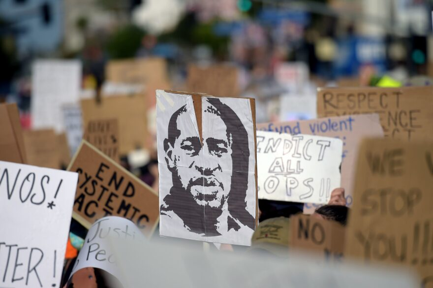 Protesters march holding placards and a portrait of George Floyd during a demonstration against racism and police brutality, in Hollywood, California on June 7, 2020. (Photo by AGUSTIN PAULLIER/AFP via Getty Images)