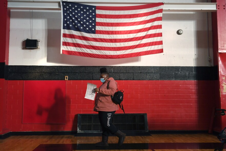 A voter casts a ballot on Tuesday at Jennings Senior High School in Jennings, Mo., a St. Louis suburb. Voters passed an amendment to Missouri's constitution that opens the door to redrawing state legislative districts that don't take into account children, noncitizens and other residents who are not eligible to vote.