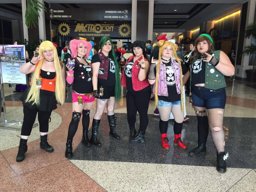 A group of six women in punk versions of Sailor Moon costumes pose in the convention hall at METROCON.